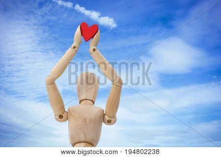 Wooden three dimensional figurine holdingred heart on top against low angle view of cloudy sky