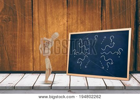 Wooden 3d figurine standing with hands on back against black board on a wooden table
