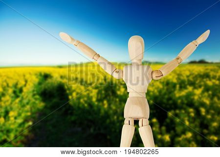 3d image of arms raised wooden figurine  against yellow mustard field