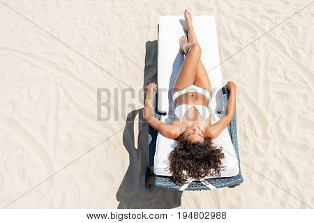 Hot pleasure. Top view of calm young beautiful mulatto girl lying on lounger on sand under burning sun. She is taking tan in bikini. Copy space in left side poster