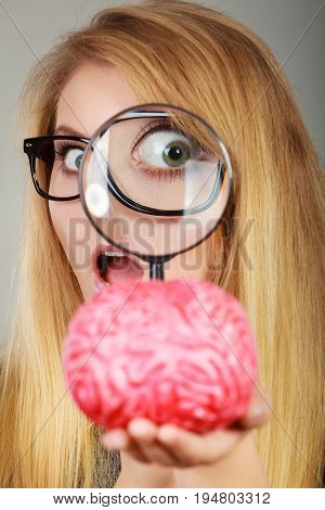 Woman Holding Magnifying Glass Investigating Brain