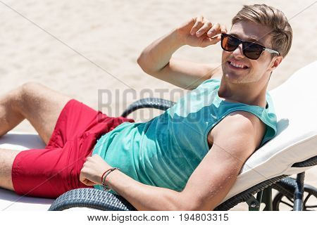 Portrait of joyful young guy in sunglasses lying on sunlounger on beach. He is smiling broadly and enjoying sunny day on seashore
