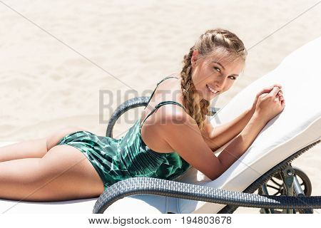 Portrait of jolly young lady lying on sunlounge on beach in bikini. She is taking tan