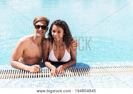 Waist up portrait of cheerful young man and woman standing waist deep in swimming pool and smiling broadly. Guy is hugging her girlfriend by shoulder. Copy space in right side