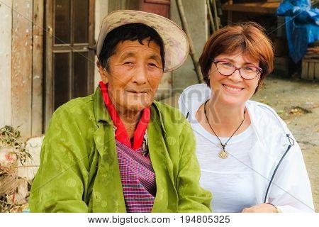 Punakha Bhutan - September 10 2016: Beautiful smiling Caucasian woman sitting with an elderly Bhutanese woman near a street market.