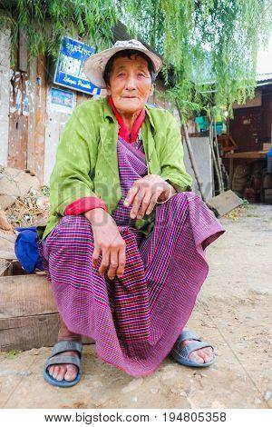 Thimphu Bhutan - September 10 2016: Elderly Bhutanese woman sitting in the street near street marketplace.