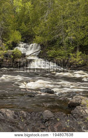 Current River Falls - A waterfall emptying into a river.