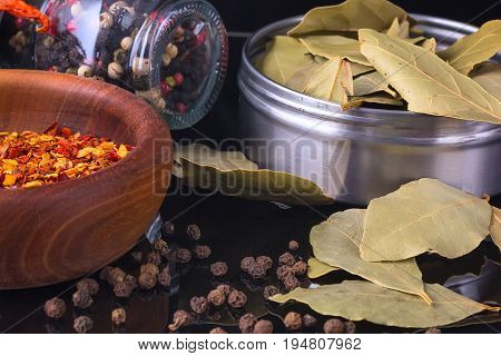 Spices and herbs, bay leaf, black peppercorn and wooden bowl of chili flakes on black background with reflection