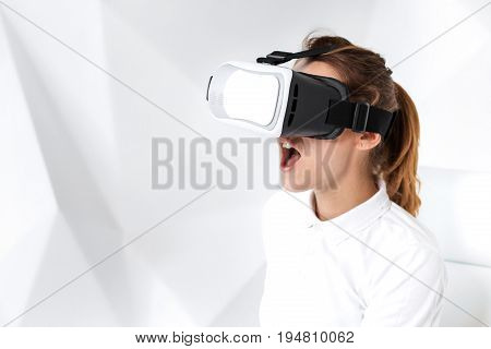 Technology, virtual reality, entertainment and people concept - happy young woman with virtual reality headset sits on a white armchair in a room with white walls