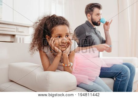 Dreamy African American Girl Sitting On Sofa And Father Drinking From Toy Cup