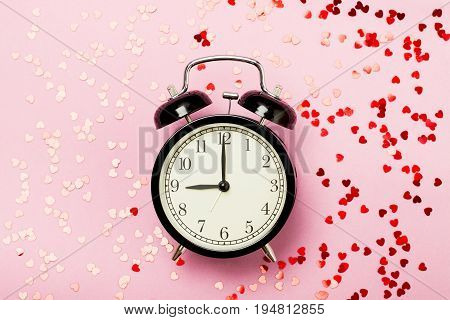 Alarm clock on a pink background with small hearts. The concept of the time of love the time of date the wedding the day of St. Valentine