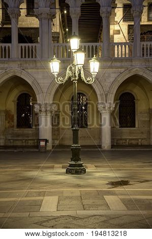 A lone street light in front of a palace in Venice.