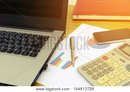 close up business accessories laptop calculator datasheet pen notebook and smartphone on desk financial report saving and economy business concept sunlight effect soft focus selective focus