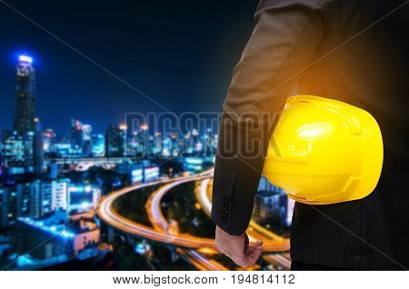 businessman or project manager hold in hand yellow safety helmet industrial concept on blurred night city background industrial business technology concept
