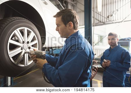 Fulfilling task. Focused scrupulous experienced mechanic using professional equipment for putting bolts on their places while changing tires