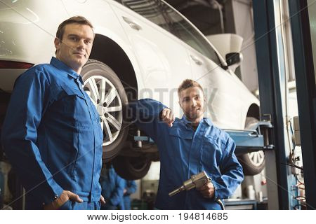 Two colleagues. Industrious serious talented servicemen standing by the auto and deciding what doing next after fixing the wheel