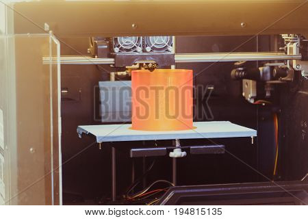 3D printer prints the form of molten plastic orange close-up. Automatic three dimensional 3d printer performs plastic modeling in laboratory. Progressive modern additive technology