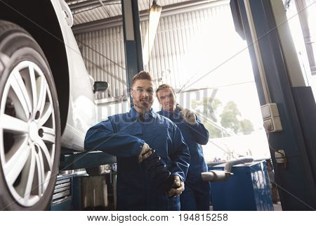 Modern workshop. Reliable prominent local tinkers holding the parts of the vehicle they repairing and posing standing near each other