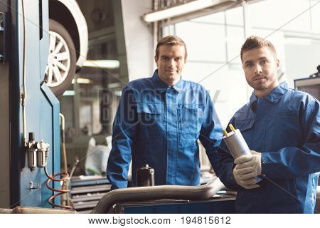Local team. Hardworking smart industrious servicemen having a little consultation discussing some work issues while repairing clients car