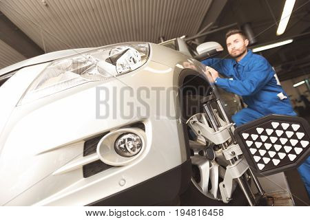 Up to date technologies. Successful determined car expert employing special tools for fixating autos wheels while performing a maintenance in garage