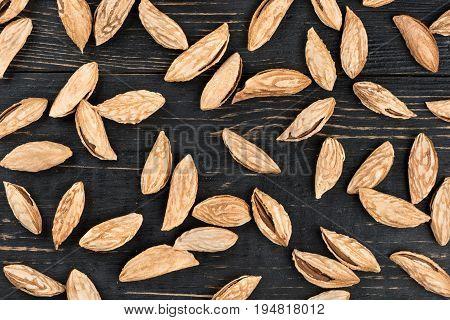 Scattered uzbek inshell almonds on wooden background
