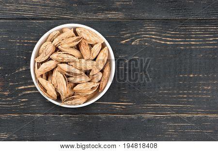 Ceramic bowl filled with Uzbek inshell almonds on wooden background