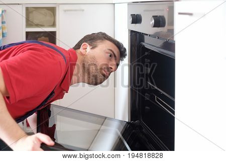 Worker Repairing The Oven In The Kitchen