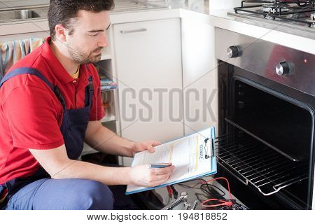 Worker Estimating Cost For Broken Oven