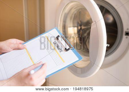 Worker Estimating Cost For Broken Washing Machine