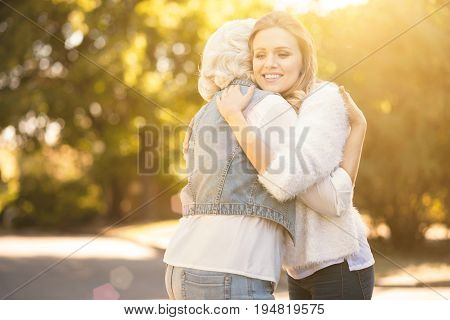 Full of amusement. Delightful young charming woman walking in the park while expressing love and hugging aged mother