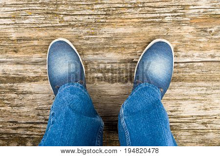 Legs in jeans and jeans shoes on an old wooden background