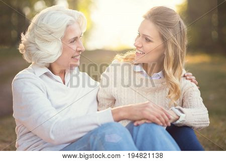 Having conversation outdoors. Attentive easygoing young woman enjoying picnic and expressing love while talking to old mother
