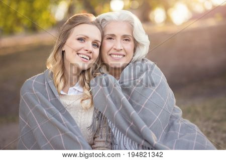 Sharing happy feelings. Merry loving young woman enjoying picnic and expressing feelings while covering with blanket and hugging aging mother