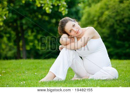 schöne schwangere Frau entspannenden im park