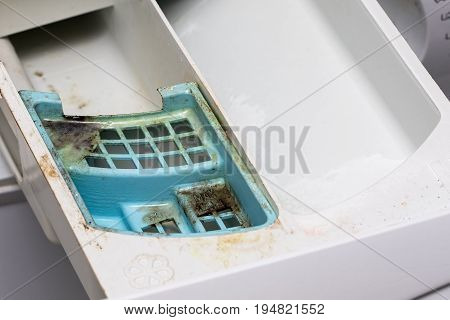 Dirty mouldy washing machine detergent and fabric conditioner dispenser drawer. Mold and dirt in washing machine.