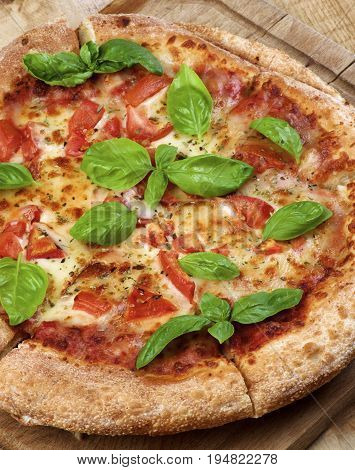 Freshly Baked Margarita Pizza with Tomatoes Cheese and Basil Leafs on Cutting Board Cross Section on Wooden background