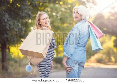 Full of grace. Happy playful pregnant woman walking in the park while expressing delight and enjoying purchases with retired mother