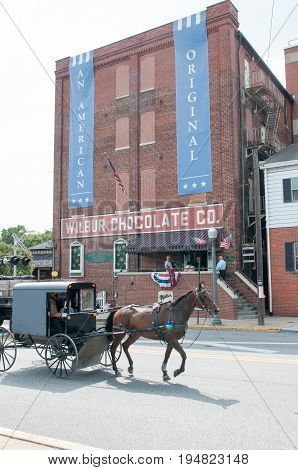 LITITZ, PA - AUGUST 30: View of Amish horse and buggy riding past the famed Wilbur Chocolate Company headquarters on Route 501 in Lititz on August 30, 2014