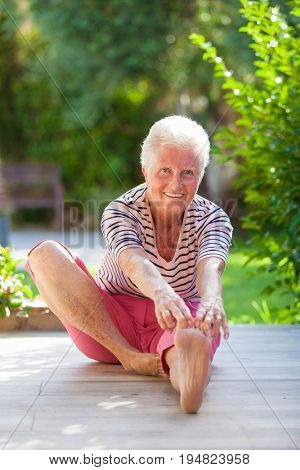 fit active pensioner stretching, touching toes.
