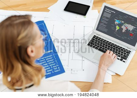 Enjoying full dedication to job. Optimistic gifted professional engineer working on the project and preparing the pencil draft while using laptop