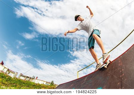 Young boy doing a trick on a ramp in a skatepark. Photo with a place for copy-space