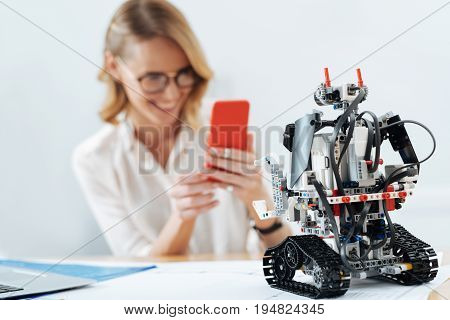 Representing tech innovations of new century. Innovative automatic artificial robot standing on the table in the office while woman using smartphone on the background and taking photo
