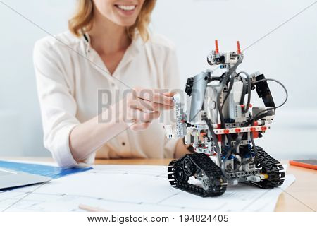 Making friends with robot. Delighted positive glad woman smiling and working in the office while looking at the electronic robot and making friends with it