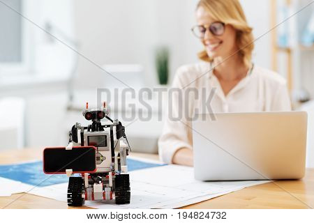 Helping people in ordinary stuff. Skilled automatic helpful robot standing on the table in the office and holding smartphone while engineer using laptop on the background and smiling