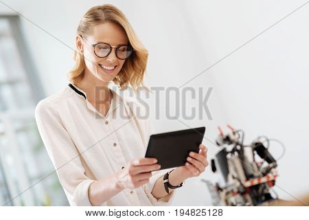 Delighted from modern technologies. Happy smiling positive woman working in the office and using digital gadget while electronic robot standing in the background