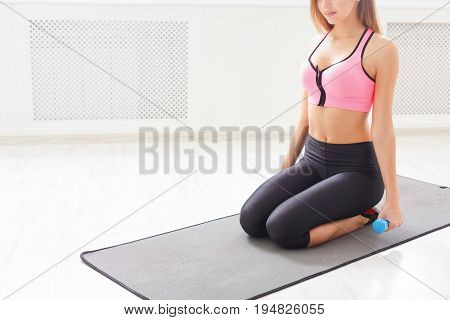Fitness woman with dumbbells sitting on mat. Unrecognizable girl in fitwear with sport equipment. Bodybuilding, healthy lifestyle concept