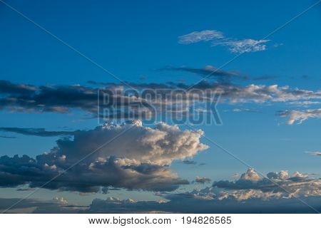 bright blue sky , puffy white clouds, sunset