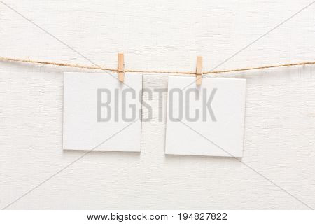 White blank cards on rope, copy space. Creative reminder, small sheets of paper on clothespin, light memo background