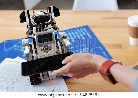 Mastering human skills . Programmed electronic innovative robot standing on the table in the laboratory and holding tablet while helping human