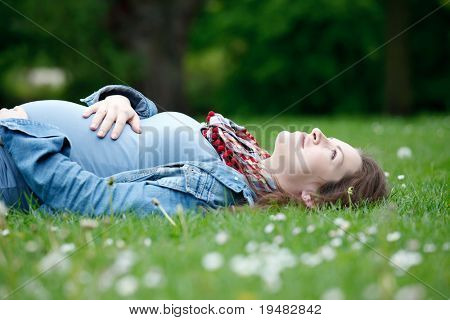 Beautiful pregnant woman relaxing on grass